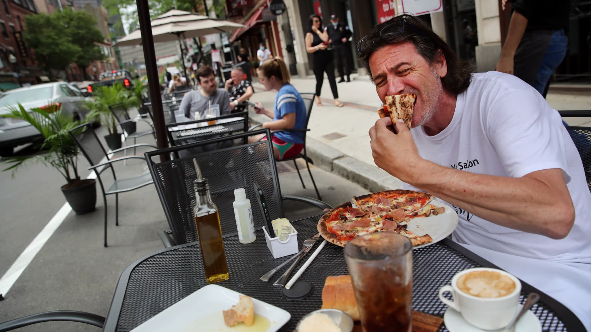 Johnny D'agostina digs into a pizza outside Quattro restaurant on Hanover Street in the North End neighborhood of Boston, MA on June 11, 2020.