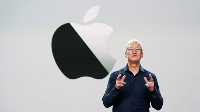 Apple CEO Tim Cook delivering a keynote with Apple's logo in the back