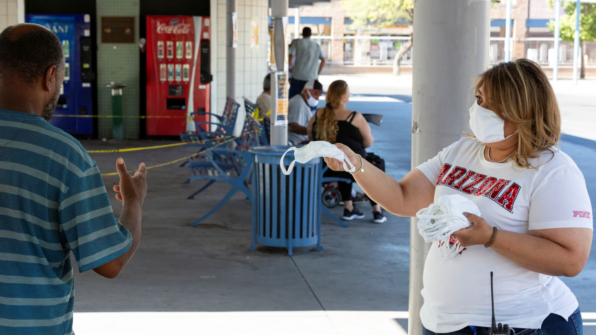 A Sun Tran employee offers free masks to passengers to prevent the spread of the coronavirus disease (COVID-19), at the downtown bus station in Tucson, Arizona, U.S., June 20, 2020.
