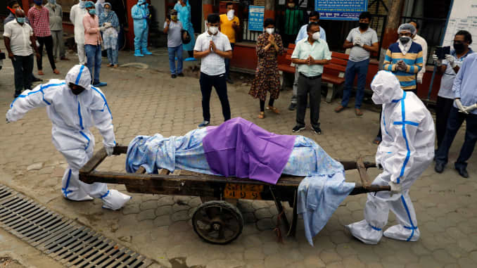 Health workers wearing Personal Protective Equipment (PPE) carry the body of a person who who died due to the coronavirus disease (COVID-19), at a crematorium in New Delhi, India, June 24, 2020.