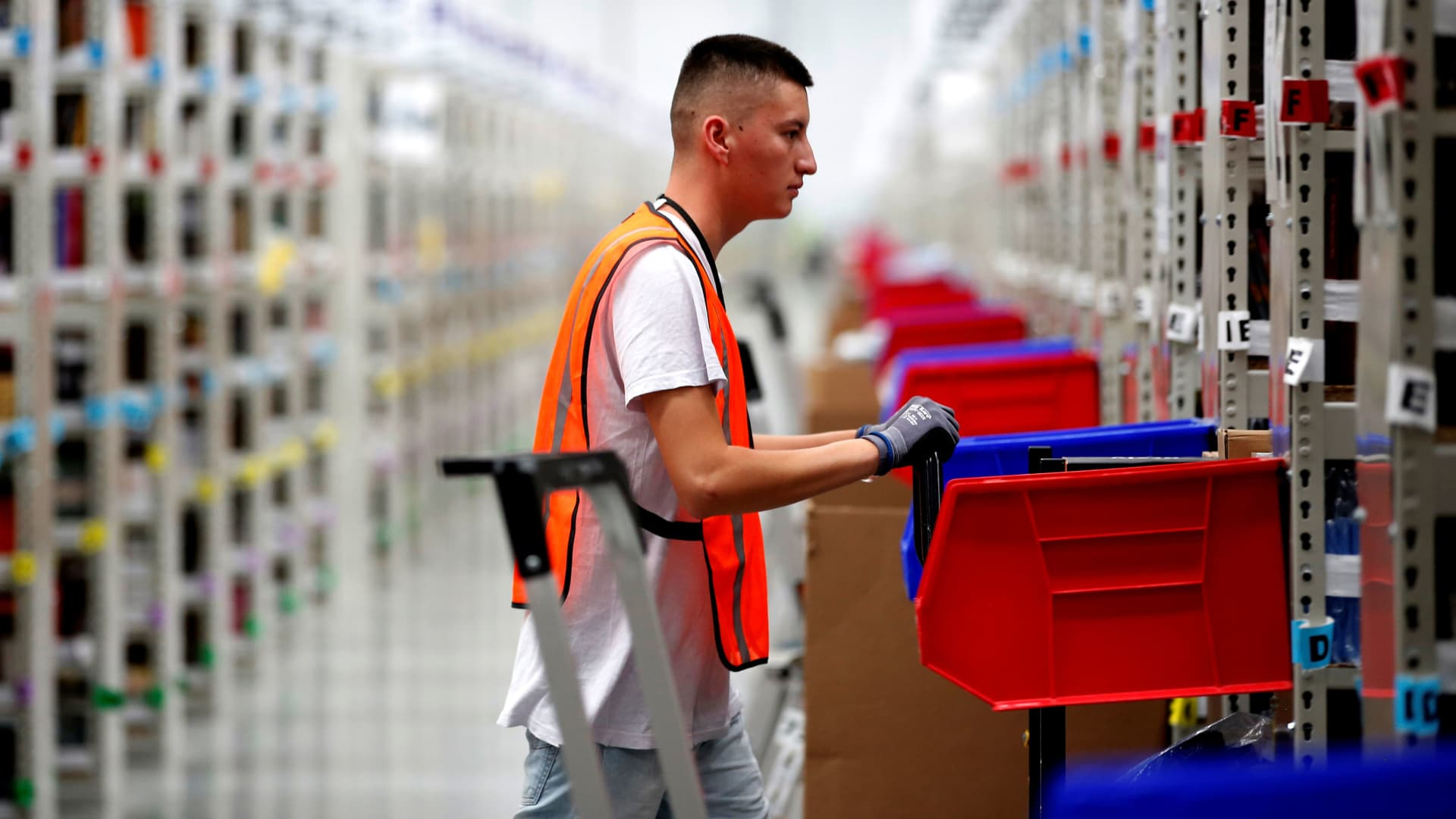 An employee looks for items in one of the corridors at an Amazon warehouse.