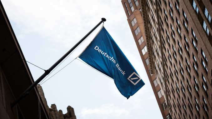 A Deutsche Bank AG flag flies outside the company's office on Wall Street in New York.