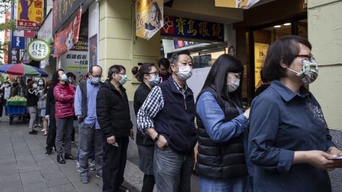 Taiwanese wait in line at a pharmacy to pick up masks, which are pre-ordered online on March 18, 2020 in Taipei, Taiwan.