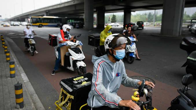 Một tài xế giao hàng đeo khẩu trang đi xe đạp điện dọc theo một con phố ở Khu Thương mại Trung tâm ở Bắc Kinh vào ngày 16/7/2020.
