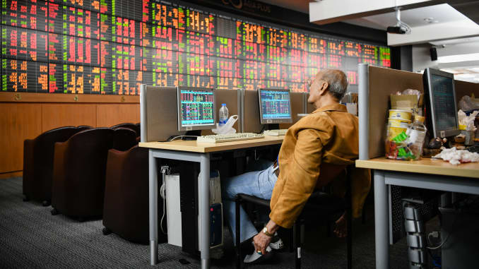 A Thai investor checks an electronic board showing stock prices at Asia Plus Securities amid Coronavirus threats in Bangkok.