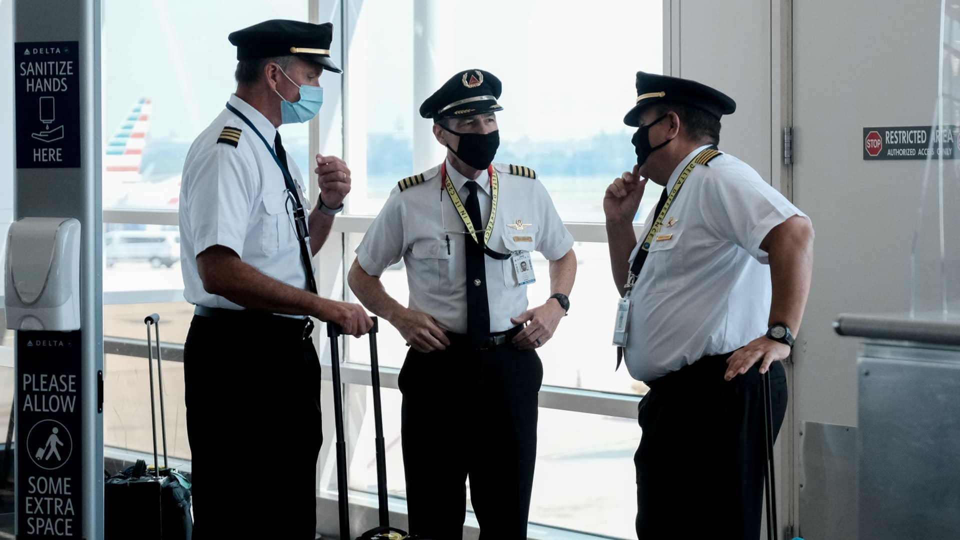 Pilots talk after exiting a Delta Airlines flight at the Ronald Reagan National Airport on July 22, 2020 in Arlington, Virginia.