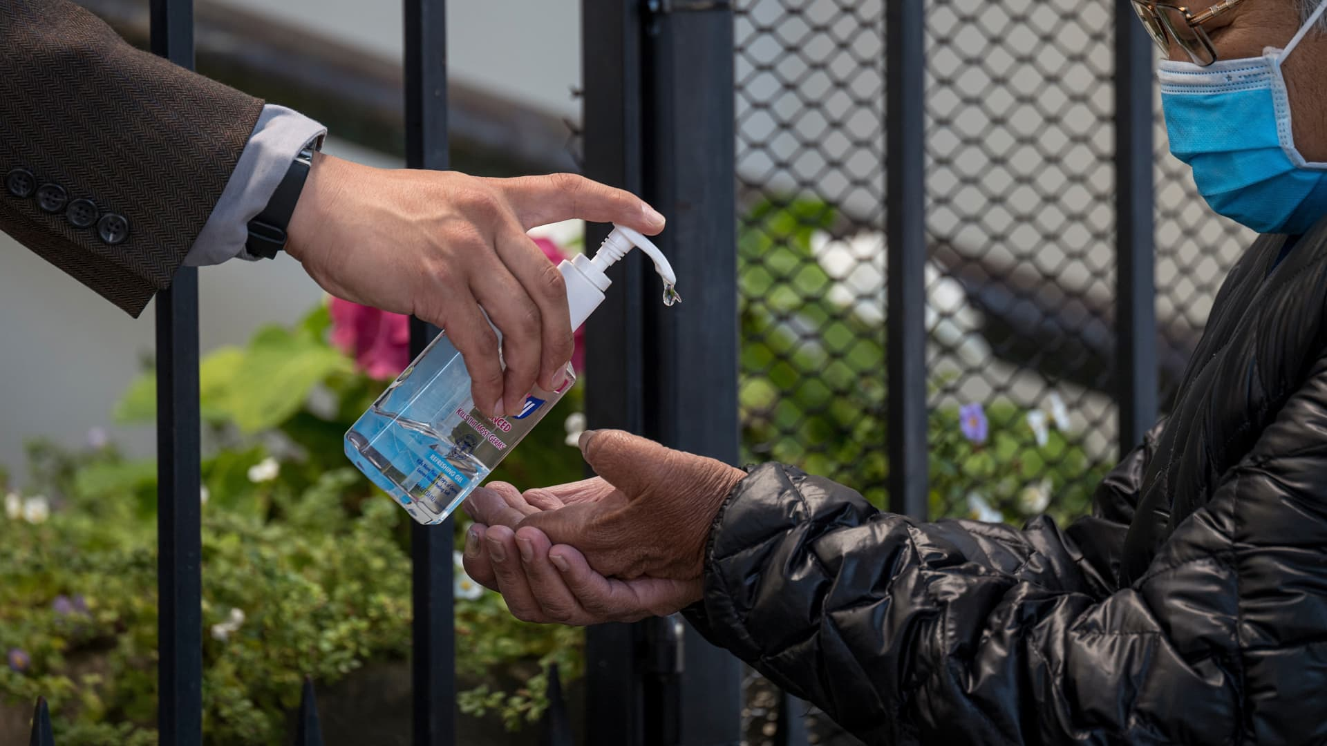 A person wearing a protective mask receives hand sanitizer while attending mass outside the National Shrine of St. Francis of Assisi Catholic Church in San Francisco, California, on Tuesday, July 14, 2020.