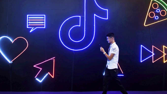 A man holding a phone walks past a sign of Chinese company ByteDance's app TikTok, known locally as Douyin, at the International Artificial Products Expo in Hangzhou, Zhejiang province, China October 18, 2019.
