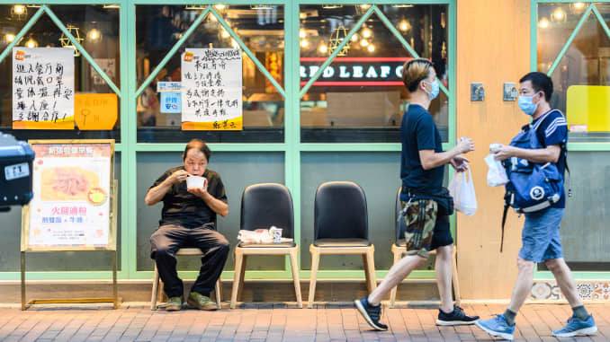 A man eats a takeaway meal on a chair placed outside a restaurant in Hong Kong