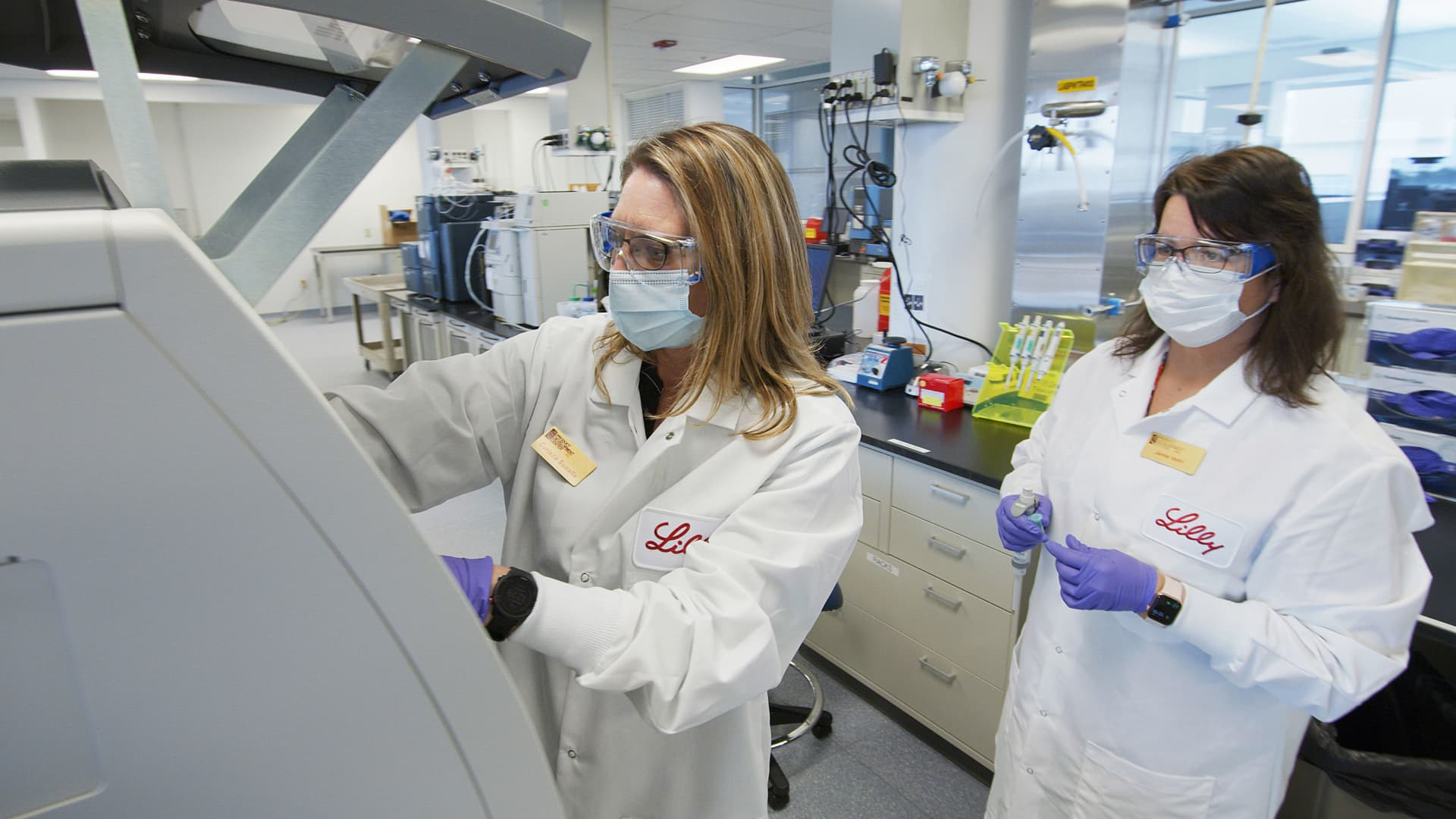 In this May 2020 photo provided by Eli Lilly, researchers prepare mammalian cells to produce possible COVID-19 antibodies for testing in a laboratory in Indianapolis.