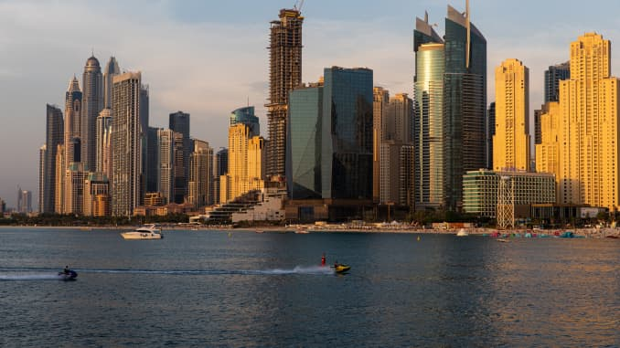 Jet skis pass by residential skyscrapers on the waterside in the Dubai Marina district in Dubai, United Arab Emirates