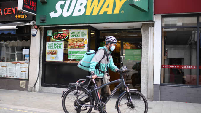 A delivery person wheels his bicycle outside a Subway shop.
