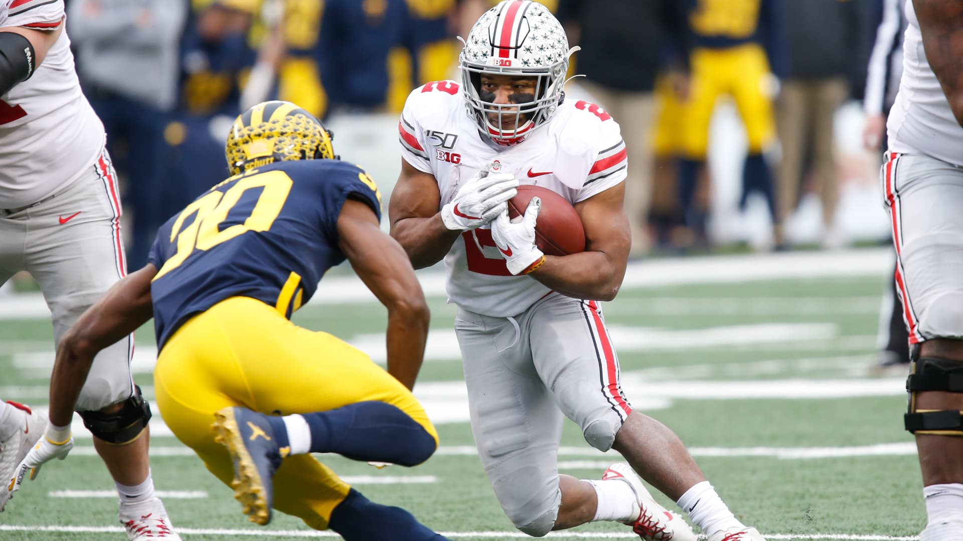 Ohio State Buckeyes running back J.K. Dobbins (2) runs with the ball while trying to avoid being tackled by Michigan Wolverines defensive back Daxton Hill (30) during a regular season Big 10 Conference game between the Ohio State Buckeyes (2) and the Michigan Wolverines.