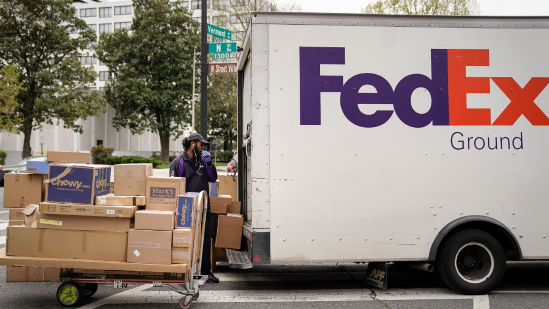 A FedEx worker unloads packages from his delivery truck on March 31, 2020 in Washington, DC.