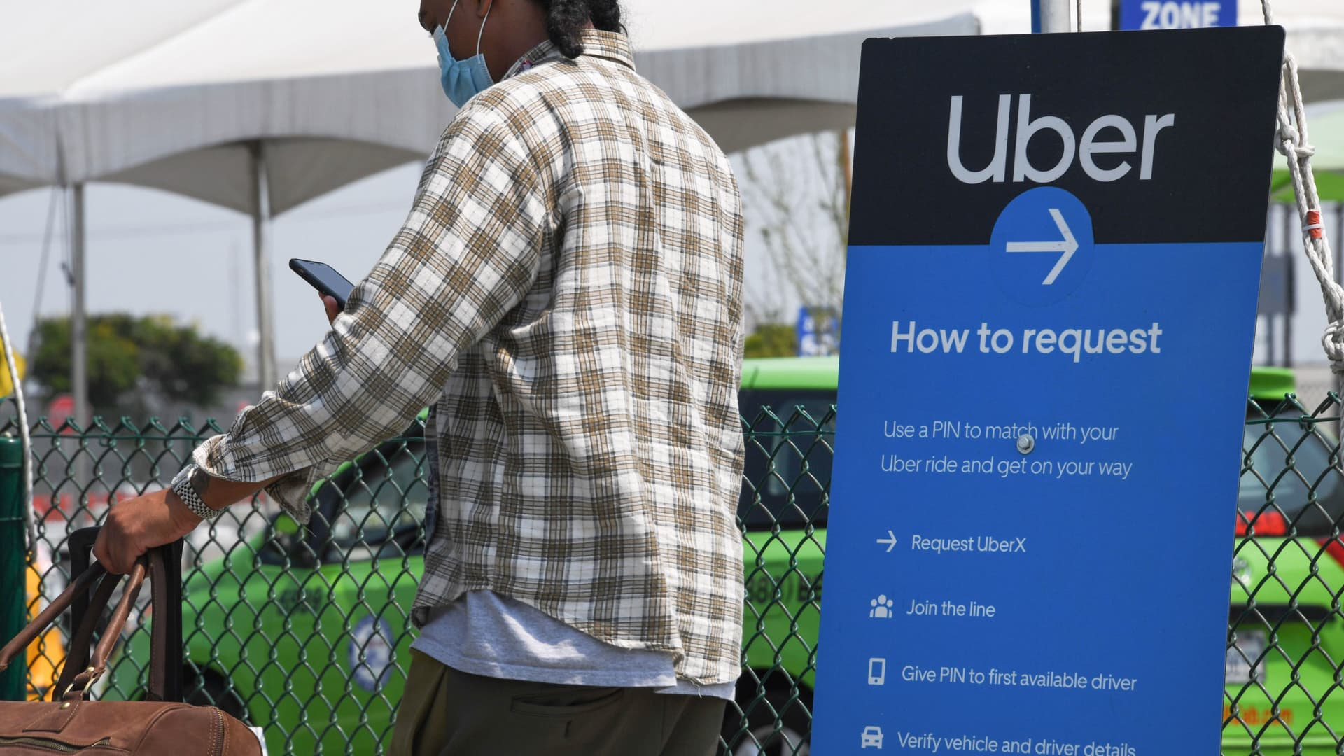A traveler checks his phone beside an Uber sign, August 20, 2020 at Los Angeles International Airport in Los Angeles, California.