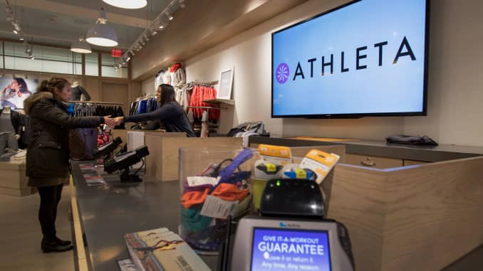 An employee rings up a customer's purchases at the Athleta store in New York.