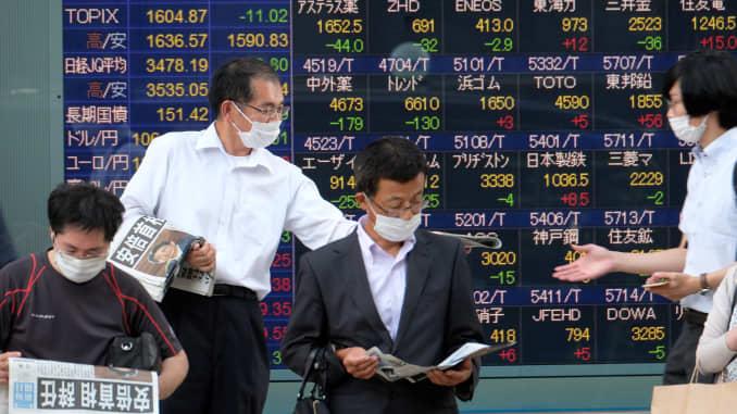 Những người đi bộ đọc một ấn bản bổ sung về việc Thủ tướng Shinzo Abe từ chức vì không có bảng báo giá điện tử hiển thị giá cổ phiếu từ Sở giao dịch chứng khoán Tokyo ở Tokyo vào ngày 28 tháng 8 năm 2020.