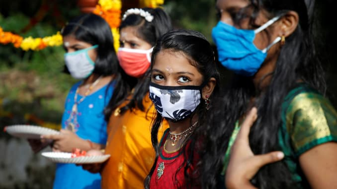 Girls wearing protective face masks wait to pray inside temple premises on the occasion of the annual harvest festival of Onam, amidst the spread of the coronavirus disease (COVID-19), on the outskirts of Kochi, India, August 31, 2020.