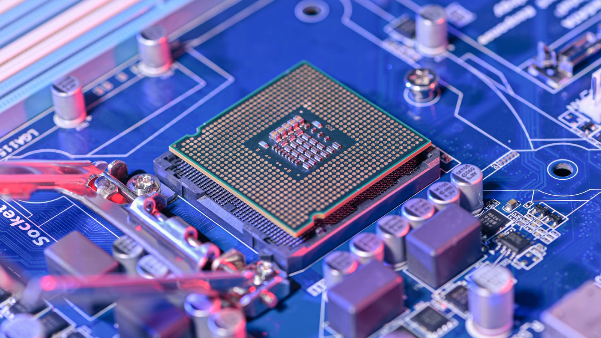 A close up image of a CPU socket and motherboard laying on the table.