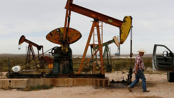 Paul Putnam, 53, a rancher and independent contract pumper walks past a pump jack in Loving County, Texas, U.S. November 25, 2019.