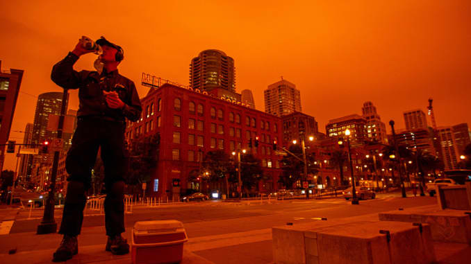Jamie Johnson, of San Francisco, takes his lunch at Embarcadero as smoky skies from the northern California wildfires casts a reddish color in San Francisco, Calif., on Wednesday, Sept. 9, 2020.