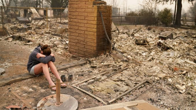 """Desiree Pierce cries as she visits her home destroyed by the Almeda Fire, Friday, Sept. 11, 2020, in Talent, Ore. """"I just needed to see it, to get some closure,"""" said Pierce."""