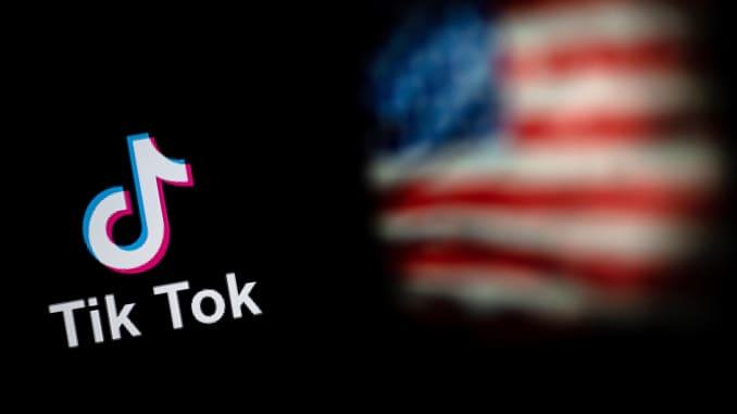 Hình ảnh minh họa được chụp vào ngày 14 tháng 9 năm 2020 này cho thấy logo của ứng dụng mạng xã hội TikTok (L) và một lá cờ Hoa Kỳ (R) được hiển thị trên màn hình của hai máy tính xách tay ở Bắc Kinh.