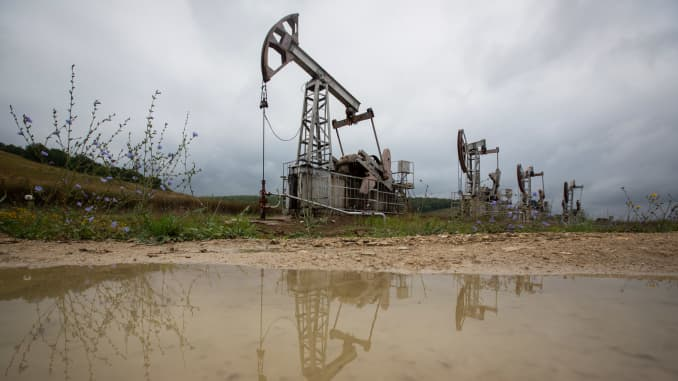 "Oil pumping jacks, also known as ""nodding donkeys"", are reflected in a puddle as they operate in an oilfield near Almetyevsk, Russia, on Sunday, Aug. 16, 2020."