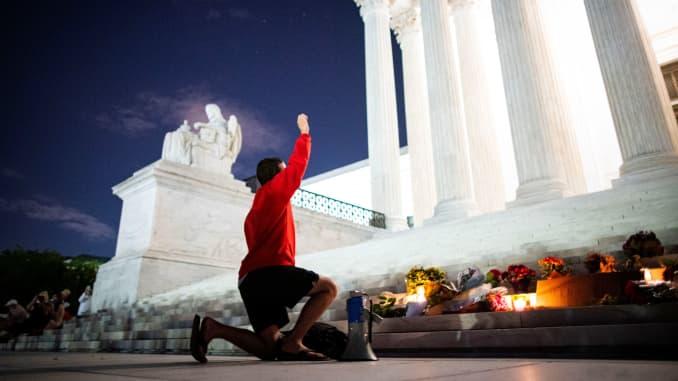 Một người đàn ông giơ nắm đấm lên trời khi anh ta đưa một chiếc loa phóng thanh trước tòa án tối cao Hoa Kỳ sau cái chết của Thẩm phán Tòa án tối cao Hoa Kỳ Ruth Bader Ginsburg, ở Washington, Hoa Kỳ, ngày 18 tháng 9 năm 2020.