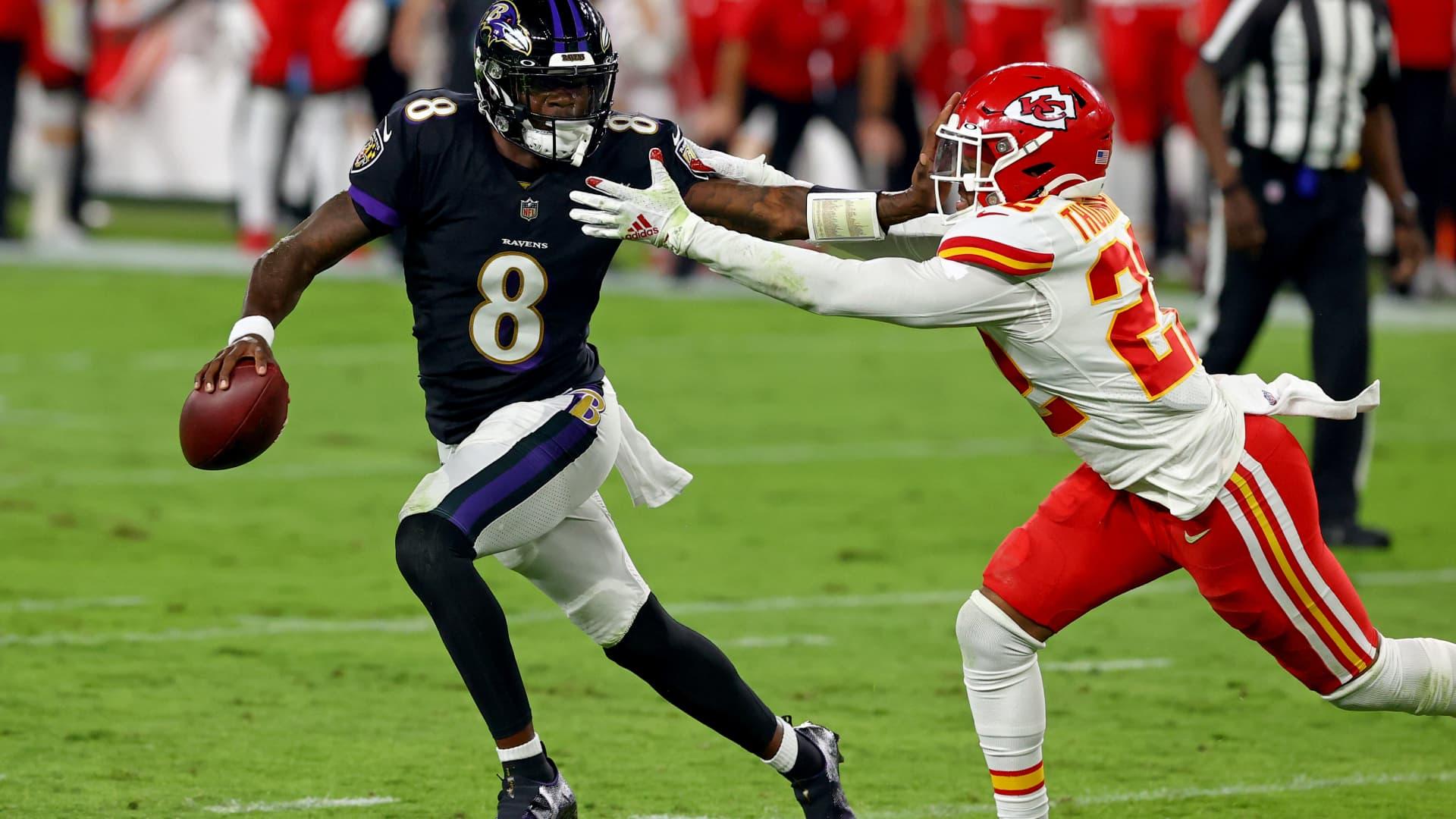 Lamar Jackson of the Baltimore Ravens, left, stiff arms the Kansas City Chiefs' Juan Thornhill at Baltimore's M&T Bank Stadium on Sept. 28, 2020.