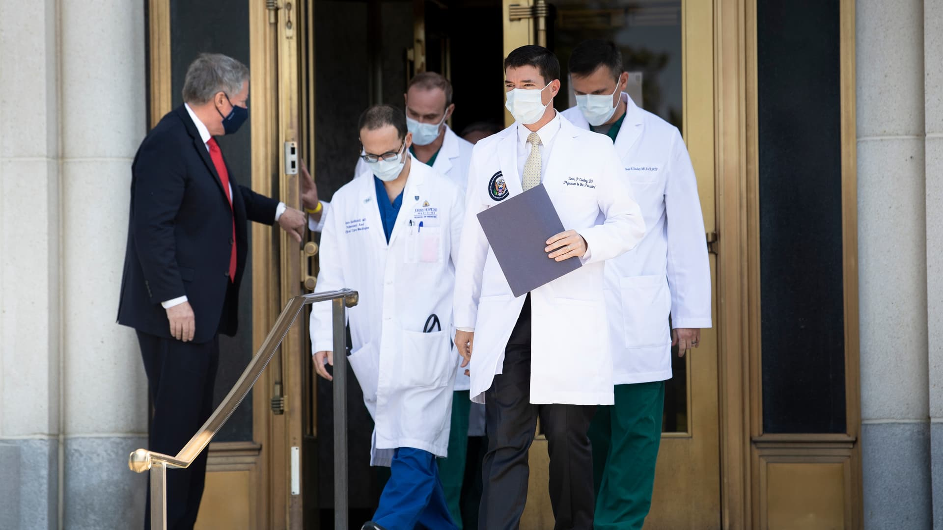 Acting White House Chief of Staff Mark Meadows holds the door for Sean Conley(front C), Physician to US President Donald Trump, and other members of the President's medical team as they arrive to give an update on the President's health at Walter Reed Medical Center during treatment for a COVID-19 infection October 4, 2020, in Bethesda, Maryland.