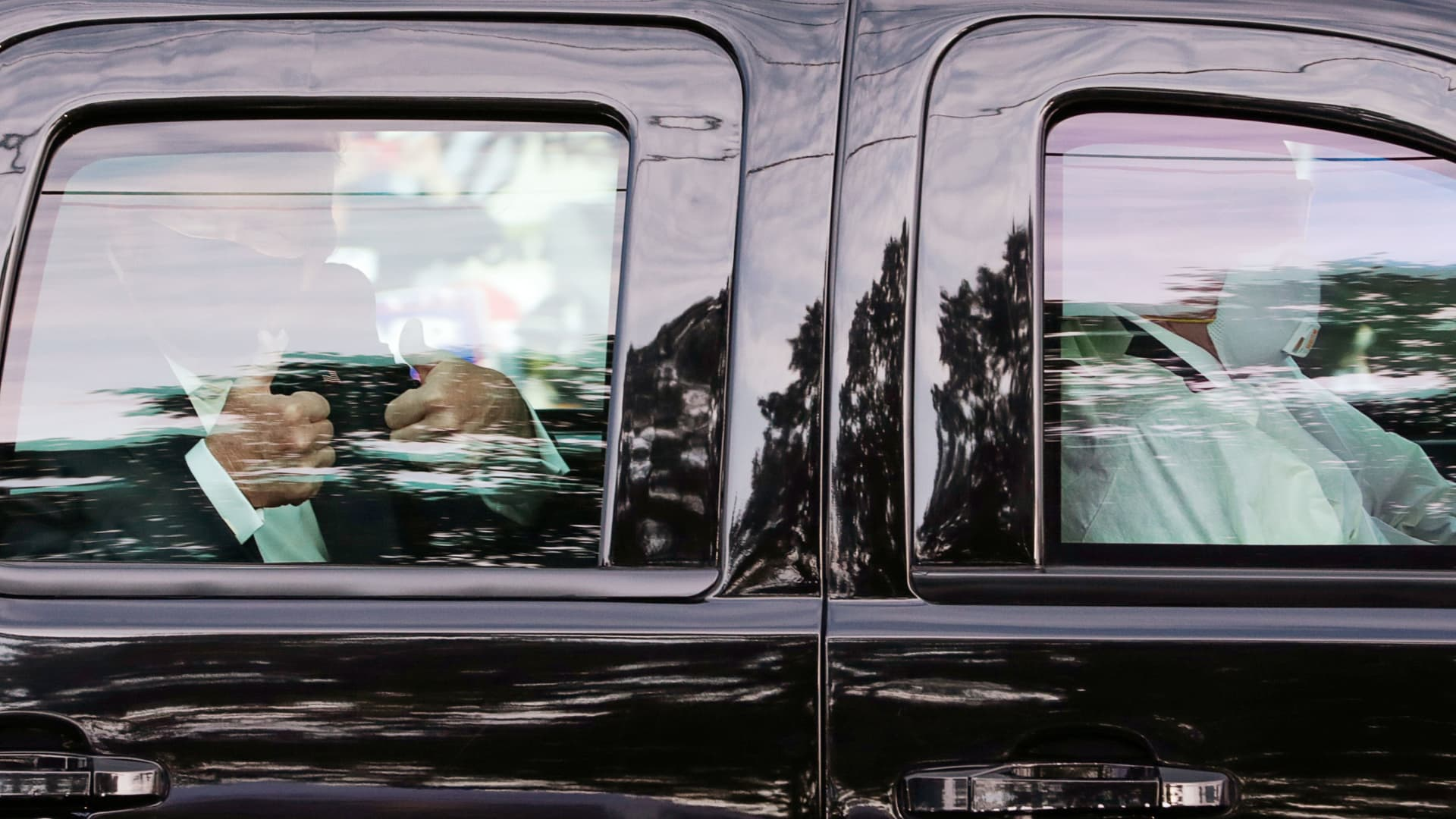 U.S. President Donald Trump gives two thumbs up to supporters as he rides in the presidential SUV with two U.S. Secret Service agents wearing medical protective masks, goggles and protective gowns in the front seat as they drive past the front of Walter Reed National Military Medical Center, where he is being treated for coronavirus disease (COVID-19) in Bethesda, Maryland, U.S. October 4, 2020.
