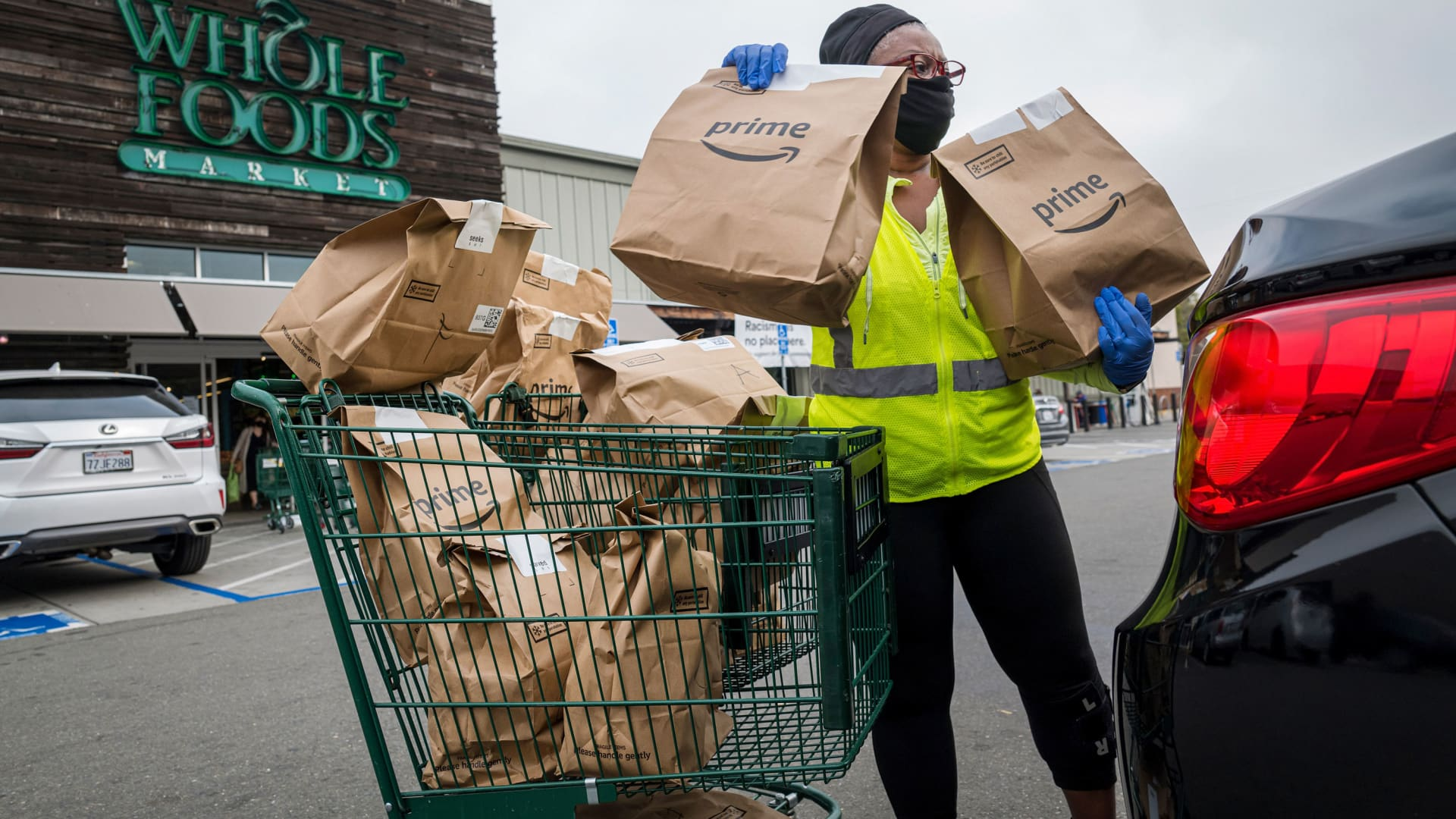 An independent contractor wearing a protective mask and gloves loads Amazon Prime grocery bags into a car outside a Whole Foods Market in Berkeley, California, Oct. 7, 2020.