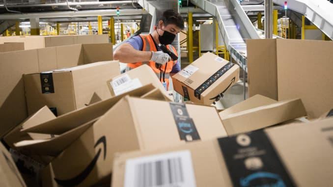 Một nhân viên đeo mặt nạ bảo vệ quét gói hàng tại trung tâm thực hiện của Amazon.com Inc. ở Kegworth, Vương quốc Anh, vào thứ Hai, ngày 12 tháng 10 năm 2020.