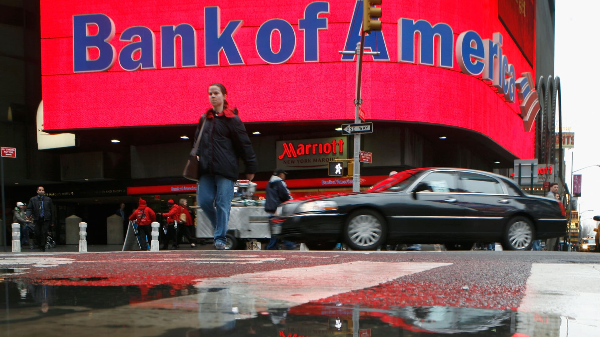 A woman is reflected in a puddle as she passes a Bank of America branch in New York's Times Square.