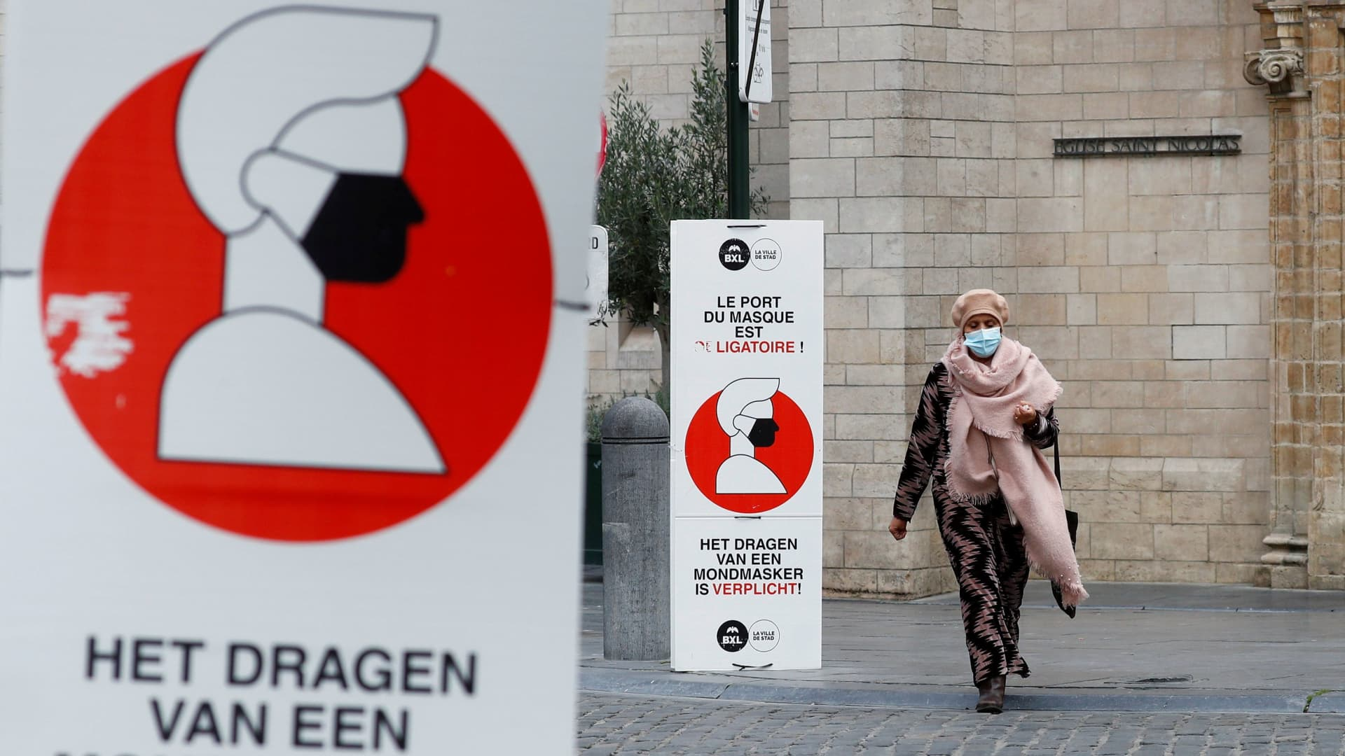 A woman walks past a sign announcing the mandatory use of masks in central Brussels as Belgian government meets to announce new restrictive measures after a spike of coronavirus disease (COVID-19) infections, Belgium October 16, 2020.