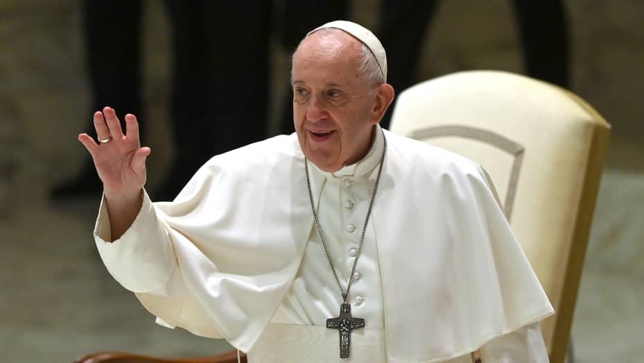 Paus Fransiskus melambaikan tangan selama audiensi umum mingguannya di aula Paulus VI di Vatikan pada 14 Oktober 2020