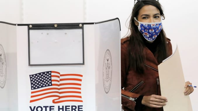 Congresswoman Alexandria Ocasio-Cortez holds her filled ballot as she votes early at a polling station in The Bronx, New York City, U.S., October 25, 2020.