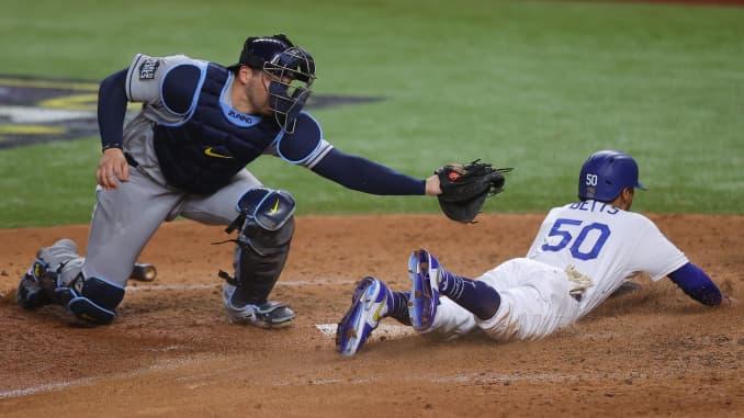 Taruhan Mookie # 50 dari Los Angeles Dodgers meluncur dengan aman melewati Mike Zunino # 10 dari Tampa Bay Rays untuk mencetak lari pada pilihan fielder yang dipukul oleh Corey Seager (tidak digambarkan) selama inning keenam di Game Enam dari Dunia MLB 2020 Seri di Globe Life F