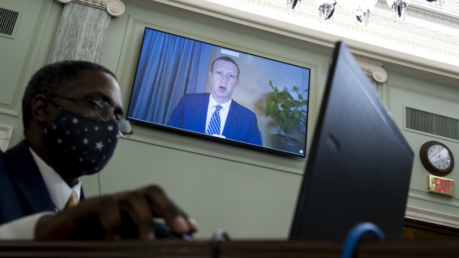 CEO of Facebook Mark Zuckerberg appears on a monitor behind a stenographer as he testifies remotely during the Senate Commerce, Science, and Transportation Committee hearing 'Does Section 230's Sweeping Immunity Enable Big Tech Bad Behavior?', on Capitol Hill, October 28, 2020 in Washington, DC.
