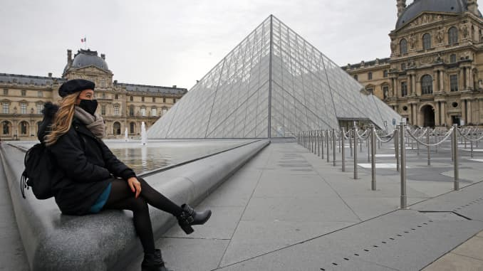 A woman wearing a protective face mask sits in front of the empty courtyard of the Louvre museum and the pyramid of Louvre as the novel coronavirus Covid-19 pandemic keeps the tourists away