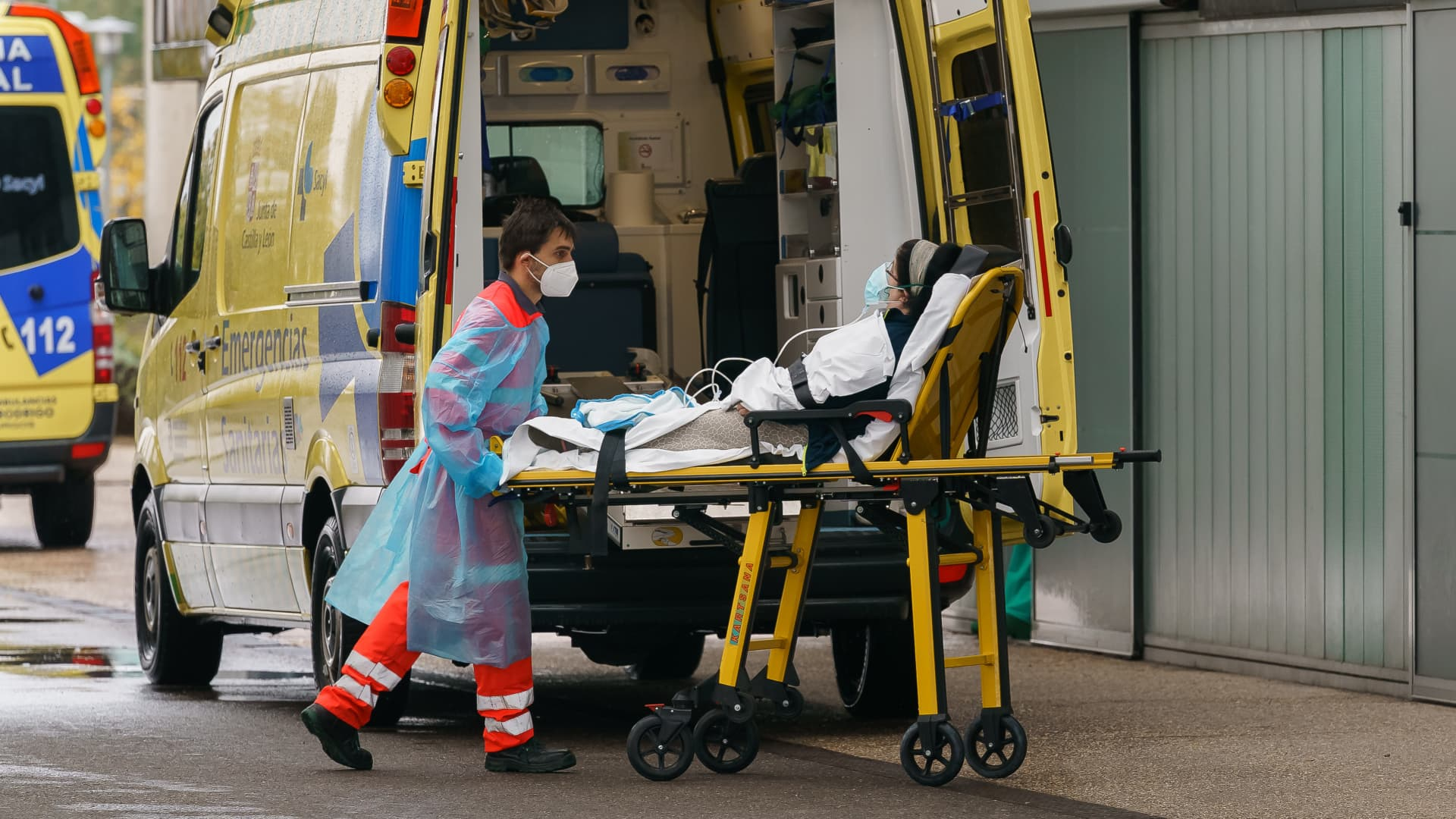 A paramedic wheels a woman out of an ambulance outside the Burgos Hospital in Burgos, northern Spain, on October 21, 2020, on the first day of a two week lockdown in an attempt to limit the contagion of the new coronavirus COVID-19 in the area.