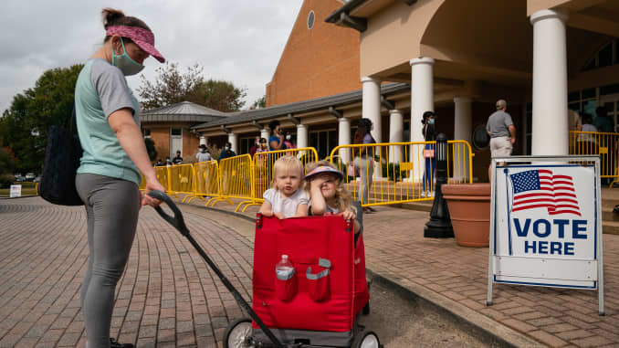 Megan Dominy pulls Brielle Taylor(L) 1, and Lila Taylor, 4, while offering water and snacks to people waiting in line to cast their ballots at an early voting location in the Smyrna Community Center on October 24, 2020, in Smyrna, Georgia.