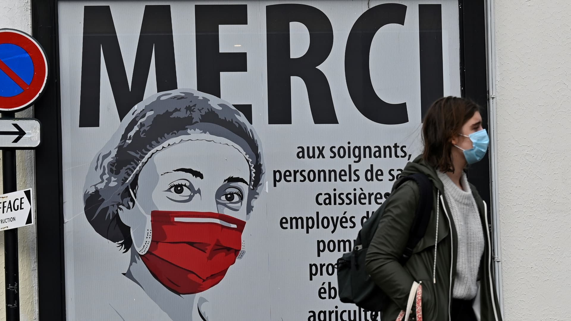 A woman walks past a poster featuring a nurse wearing a protective mask and thanking all the professions that have supported the COVID-19 coronavirus pandemic on a street in Rennes, western France on November 02, 2020, as France is under a new general lockdown to curb the spread of the Covid-19 novel coronavirus.