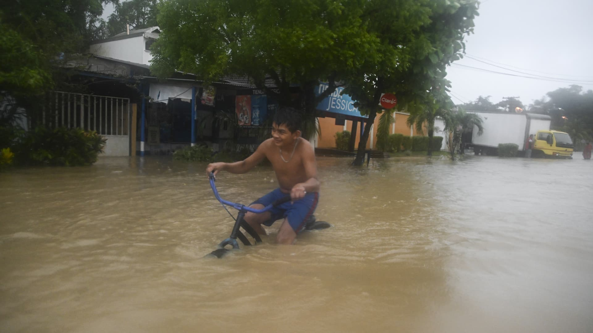A boy rides a bicycle along a flooded street due to the heavy rains caused by Hurricane Eta, now degraded to a tropical storm, in Puerto Barrios, Izabal 310 km north Guatemala City on November 5, 2020.