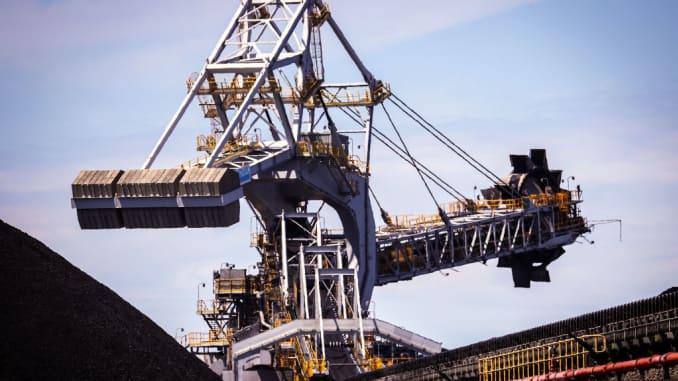 Một công nhân khai thác bánh xe xô đứng cạnh đống than tại Cảng than Newcastle, ở Newcastle, New South Wales, Australia, vào ngày 12 tháng 10 năm 2020.
