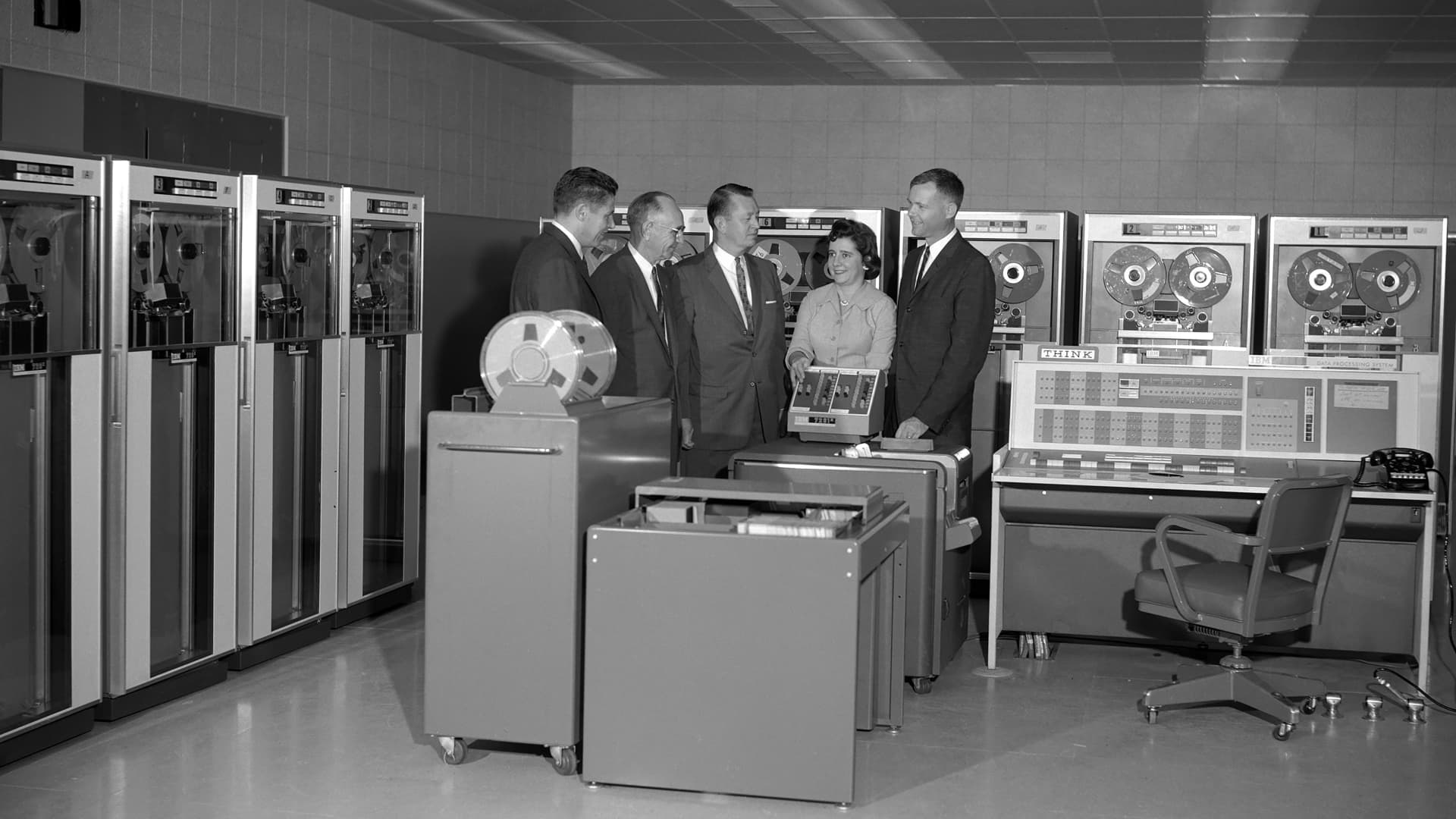 Black and white photograph of a group of IBM and government personnel in Silicon Valley, Mountain View, California, on September 20, 1961, standing next to the console of the IBM 7090 computer, which was used in early NASA space programs.