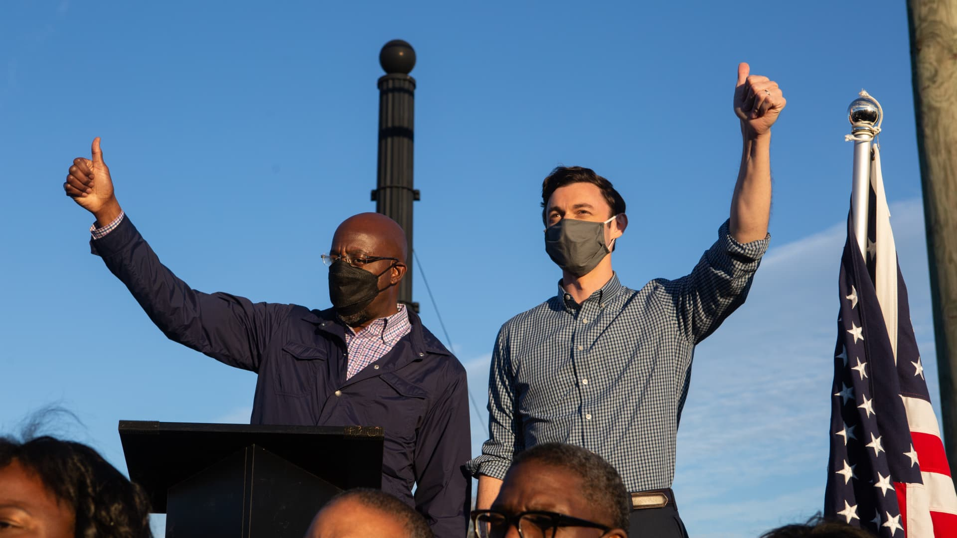 Democratic U.S. Senate candidates Jon Ossoff (R) and Raphael Warnock (L) of Georgia wave to supporters during a rally on November 15, 2020 in Marietta, Georgia.