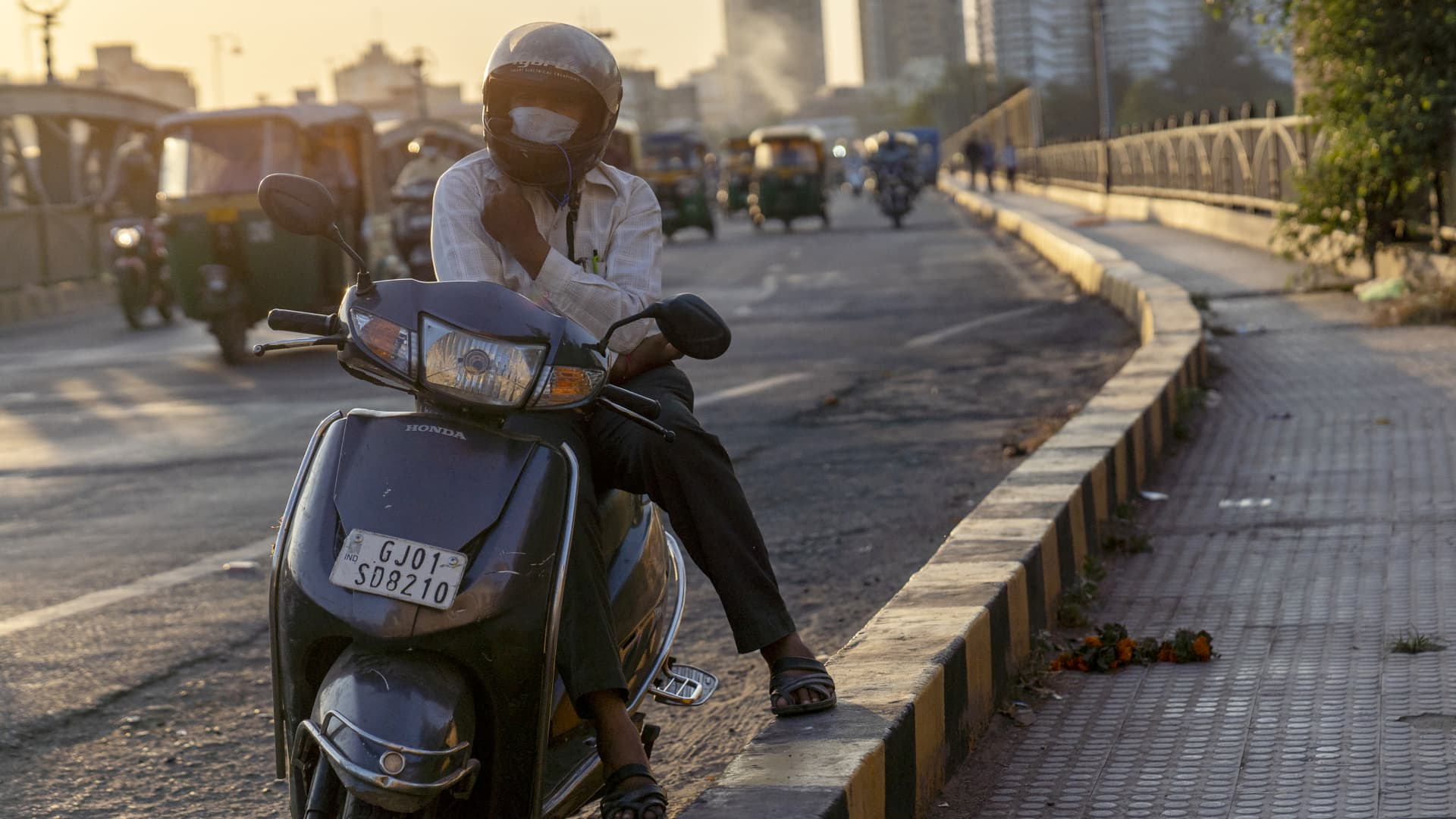 A motorcyclist wears a protective mask while sitting at the side of the road at the Sabarmati Riverfront in Ahmedabad, India, on Thursday, Oct. 22, 2020. Prime Minister Narendra Modi said his government will ensure that all 1.3 billion people nationwide will have access to a Covid-19 vaccine as soon it is ready.