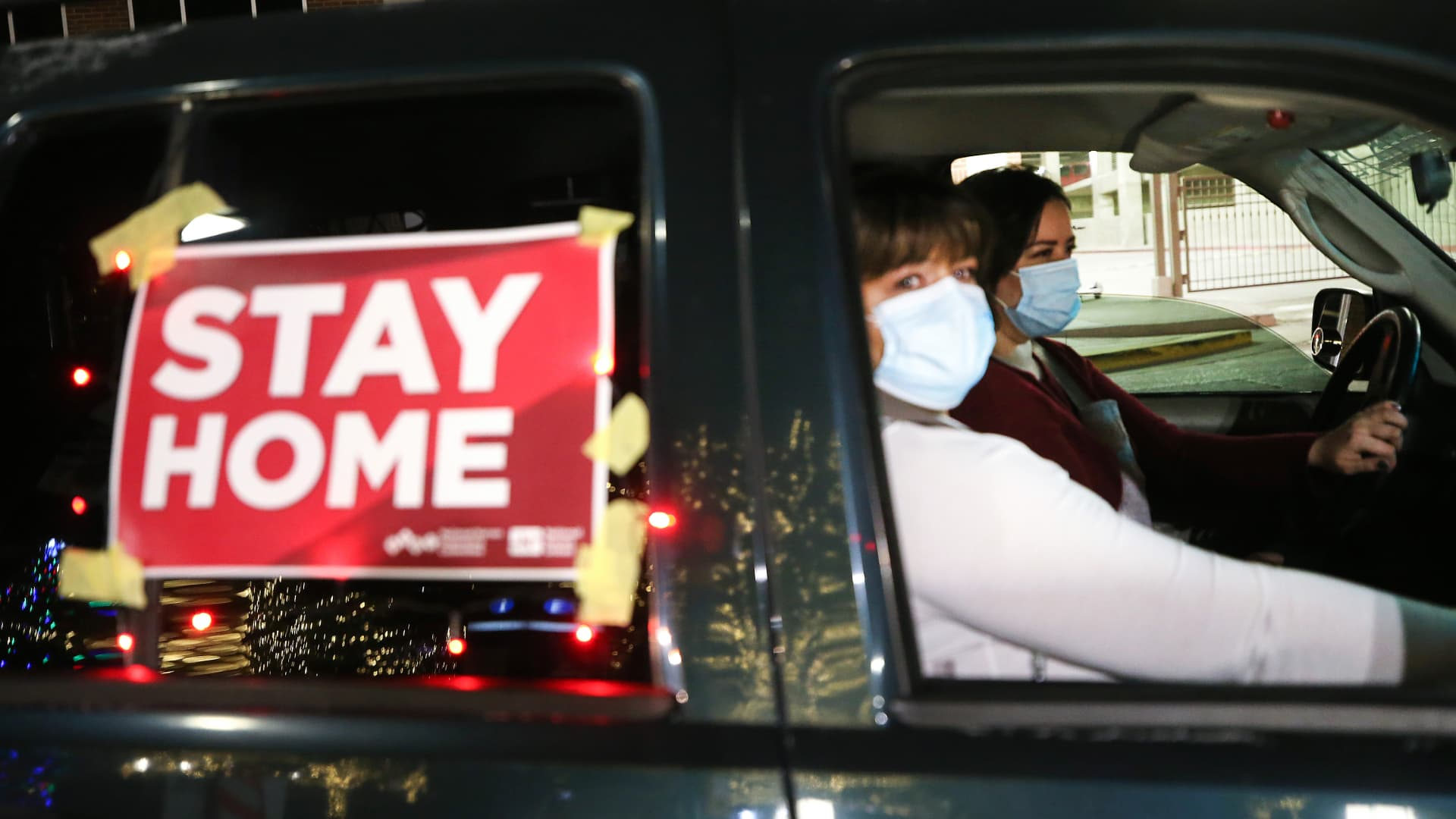 Nurses display a 'Stay Home' sign on their vehicle during a car caravan of nurses calling for people to remain home amid a surge of COVID-19 cases in El Paso on November 16, 2020 in El Paso, Texas.